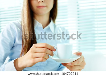 Photo of porcelain coffee cup and saucer in female hands