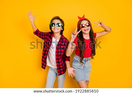 Photo of positive boy hands palms girl fingers show v-sign have good mood isolated on yellow color background Stockfoto ©
