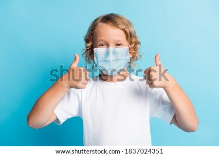 Photo of positive boy show thumb up sign wear respirator casual style outfit isolated over blue color background Photo stock ©