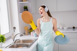 Photo of positive cheerful girl hold clean dishes wash service listen headset song enjoy rejoice cleanup chores wear yellow latex gloves in kitchen house indoors