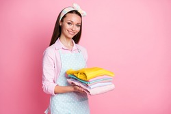 Photo of positive cheerful maid girl hold pile stack neat clothes wear good look, outfit isolated over pastel color background