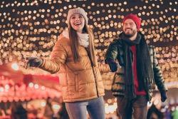 Photo of positive couple go on evening x-mas christmas jolly event, under outside shine illumination wear season outerwear