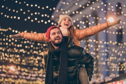 Photo of positive couple having fun christmas x-mas around evening outside illumination boyfriend piggyback girlfriend holding hands fly