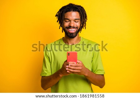Photo of positive dark skin guy use cellphone read social media news isolated over bright ahine color background Stok fotoğraf ©
