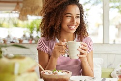 Photo of positive dark skinned mixed race female ejoys good rest at coffee shop, drinks hot beverage, has broad smile, happy to discuss something funny with friends. People, leisure and eating concept