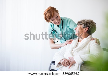 Photo of positive doctor and patient on wheelchair