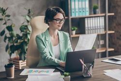 Photo of positive focused girl agent representative ceo sit table work laptop hold aim profit progress development presentation look wear blazer jacket in workplace