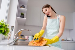 Photo of positive girl clean dirty dishes speak talk her friend smartphone call use sponge wear yellow latex gloves in kitchen house indoors