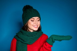 Photo of positive girl in winter season hat woolen gloves hold hand look copyspace present newyear miracle promotion wear sweater isolated over gradient blue color background