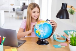 Photo of positive kid girl sit table desk study remote homeschool geography explore globe continent in house indoors