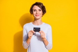 Photo of positive lady demonstrate credit card look camera wear white shirt isolated yellow color background