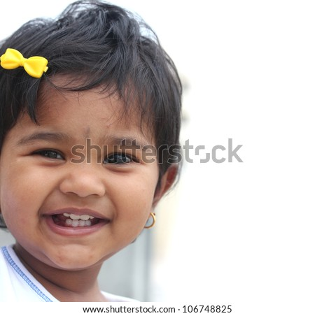 Photo of pretty and happy indian baby girl with expressive eyes and photogenic face expressing toddler's innocence with a beautiful smile. The child is of pre school/kinder-garten age.