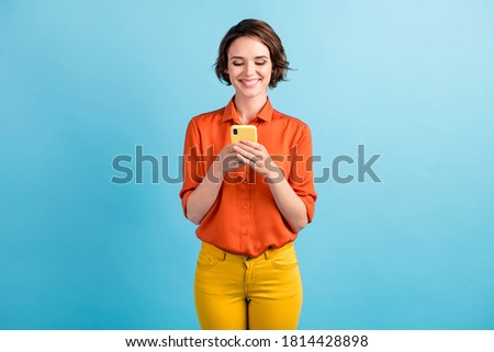 Photo of pretty attractive lady bobbed hairdo good mood chatting telephone friends writing post comments check likes reposts wear orange shirt yellow trousers isolated blue color background Сток-фото ©