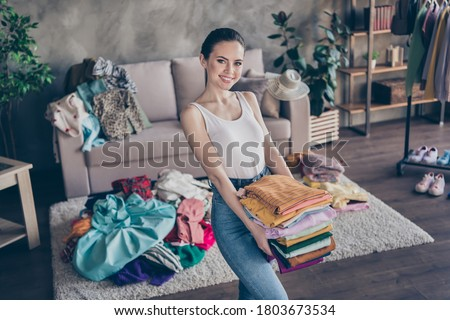 Photo of pretty charming lady stay home quarantine sorting tidy clean clothes hold hands stack wardrobe stuff donating old belongings poor people volunteer living room indoors