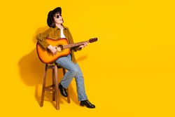 Photo of pretty charming lady wear cowgirl outfit glasses headwear playing guitar singing empty space isolated yellow color background