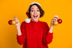 Photo of pretty cheerful funny excited lady celebrate winter holidays hold christmas balls present decorate green tree wear santa cap red knitted sweater isolated yellow color background