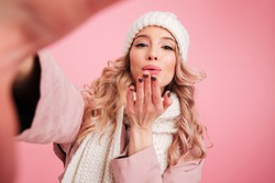 Photo of pretty cute woman standing isolated over pink background wearing warm scarf. Looking camera blowing kisses.