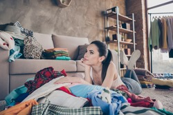 Photo of pretty dreamy lady stay home quarantine lying many clothes heap on floor wardrobe stuff spring cleaning think what to dress on date lazy carefree person living room indoors