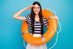 Photo of pretty excited lady long hair hold orange emergency life buoy cruise liner trip giving honor boat captain wear white striped summer dress isolated blue background