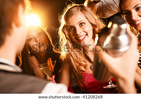 Photo of pretty girl with cocktail looking at barman at party