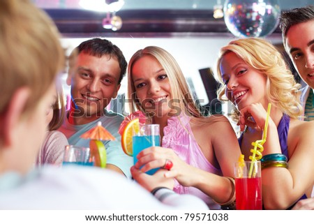 Photo of pretty girls looking at barman with guys near by