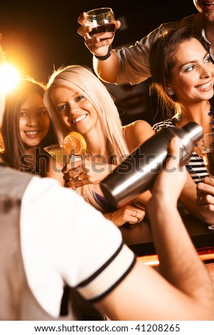 Photo of pretty girls toasting and looking at barman