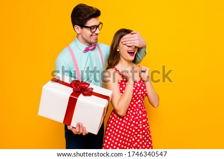 Photo of pretty lady handsome guy couple boyfriend giving girlfriend big gift box close eyes guess who game wear red dress shirt bowtie pants isolated yellow bright color background