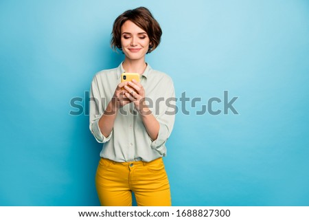 Photo of pretty lady holding telephone hands reading new blog post positive comments popular blogger wear casual green shirt yellow trousers isolated blue color background