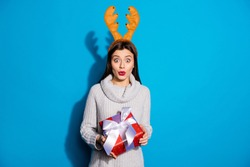 Photo of pretty lady with toy horns on her head holding red giftbox wear knitted pullover isolated blue background