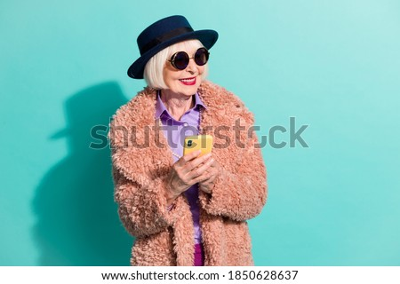 Photo of pretty senior lady wear retro jacket headwear eyeglasses writing device isolated teal color background