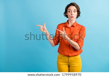 Photo of pretty shocked lady direct fingers side look interested empty space demonstrate presenting low prices poster wear orange office shirt yellow trousers isolated blue color background