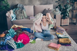 Photo of pretty stressed crying lady stay home quarantine many clothes heap stack floor wardrobe stuff pick select date outfit nothing to wear concept date preparation living room indoors