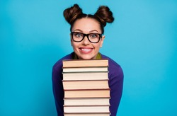 Photo of pretty student lady two funny buns leaning head chin books pile diligent pupil visit library fond of reading wear shirt pullover specs isolated blue color background