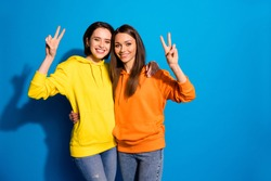 Photo of pretty two girlfriends lady showing v-sign symbols hugging wearing casual bright hoodies and jeans isolated vibrant blue color background