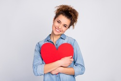 Photo of pretty wavy lady hold hands hugging red paper heart affectionate feelings toothy smile wear casual denim blue shirt isolated grey color background