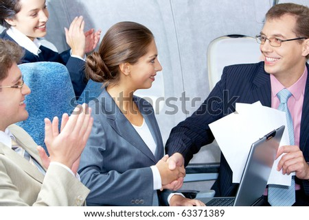 Photo of pretty woman handshaking with handsome partner after striking deal in airplane