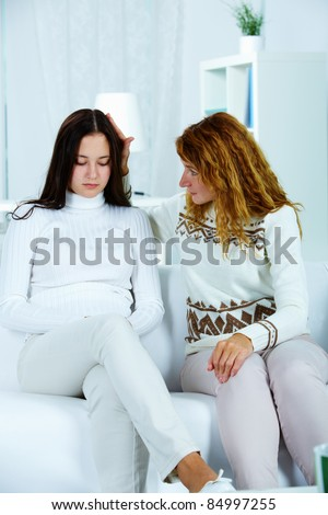 Photo of pretty woman reassuring her sad daughter