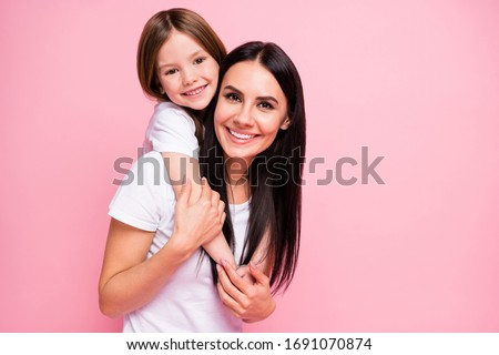Photo of pretty young mommy hold arms hugging little daughter good mood lovely sincere cardiac feelings piggyback wear casual t-shirts jeans isolated pastel pink color background