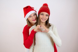 Photo of pretty young mommy hugging little daughter best friends showing heart figure wears Christmas hat isolated white background