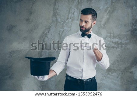 Photo of professional illusionist pretending to cast a spell to take something out of his cylindrical hat isolated over grey color wall concrete background #1553952476