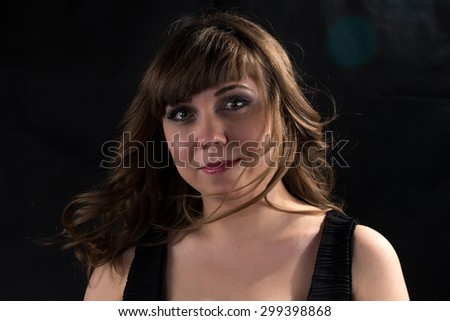Photo of pudgy woman with flowing hair on black background