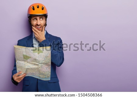 Photo of puzzled dissatisfied male engineer worker holds chin, holds blueprint, holds construction site map, works on building site, wears hard hat and blue suit, models over purple studio wall