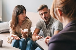 Photo of puzzled unhappy couple man and woman having conversation with psychologist on therapy session in room