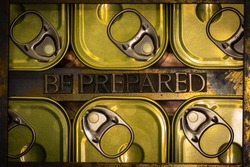 Photo of real authentic typeset letters forming capitalized Be Prepared text between canned food flatlay on vintage textured grunge copper and gold background