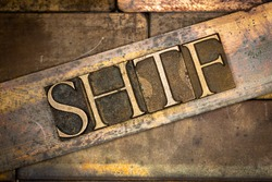 Photo of real authentic typeset letters forming capitalized SHTF text on vintage textured grunge copper background