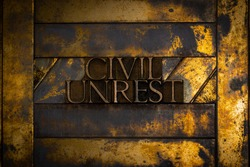 Photo of real authentic typeset letters forming Civil Unrest text on vintage textured grunge copper and gold background