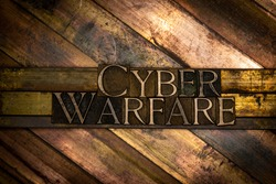 Photo of real authentic typeset letters forming Cyber Warfare text on vintage textured grunge copper background