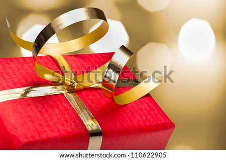 Photo of red and gold gift box with out of focus lights on a golden background