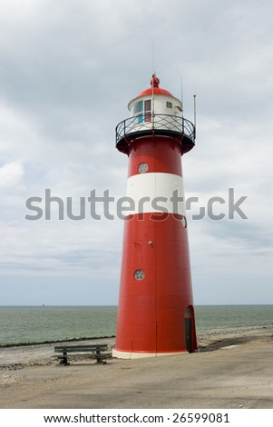 Photo of red classic lighthouse at the beach