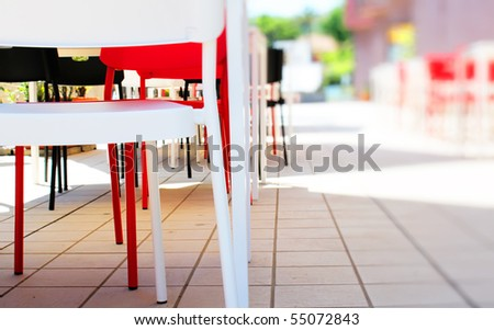 Photo of red, white and black plastic chairs in bar on open air
